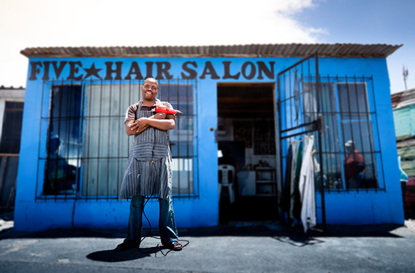 South African hairdresser in front of his saloon